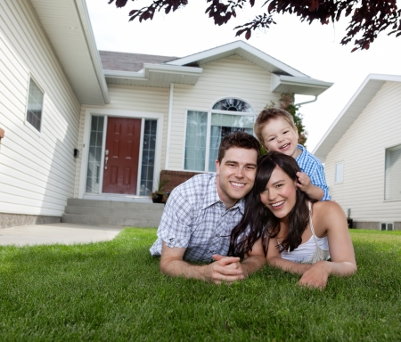 Portrait of happy family lying down on grass in front of house