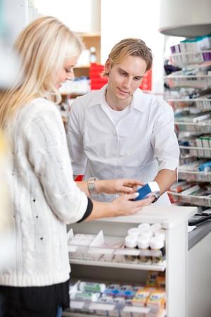 Male pharmacist helping female customer for medicine