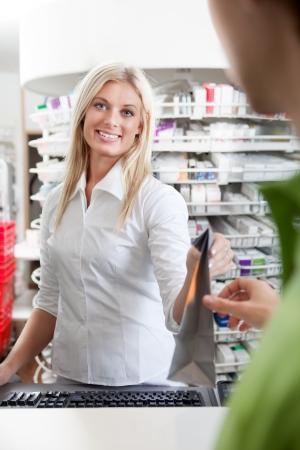 Female Pharmacist With Male Customer In Pharmacy Drugstore