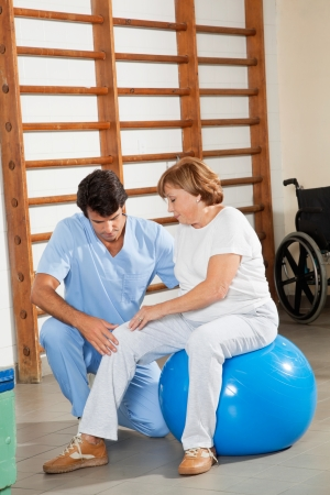 Young physical therapist examining senior woman s knee at hospital gym