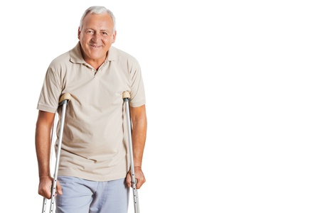 Portrait of smiling senior man on crutches standing over white background