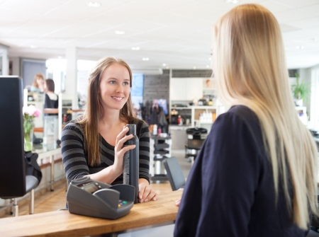 Receptionist and client in beauty salon swiping credit card