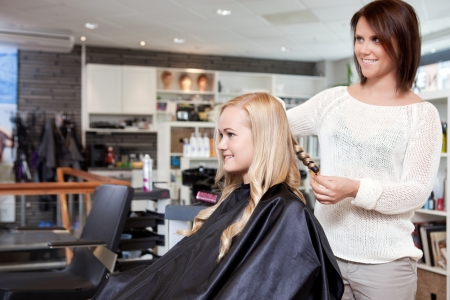 Stylist curling womans hair in beauty salon