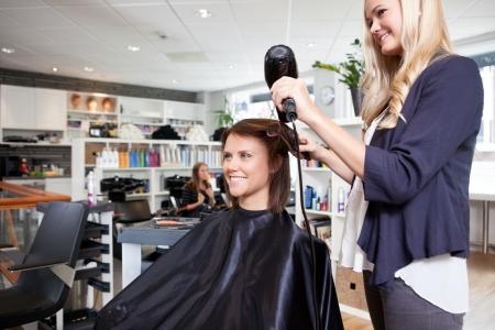 Hairdresser drying female customer s hair in beauty salon