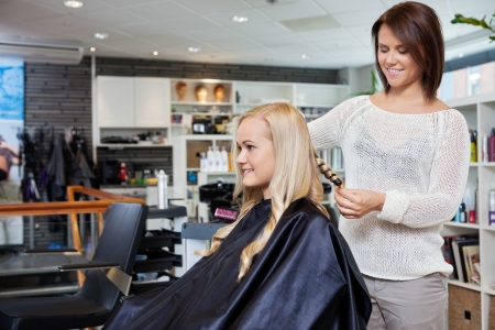 Young woman having her hair styled by beautician at parlor