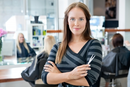 Portrait of a confident female hairdresser standing hands folded with people in background