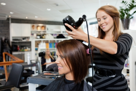 Beautician blow drying woman s hair after giving a new haircut at parlor