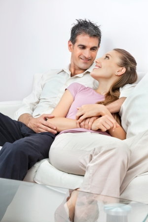 Happy couple looking at each other while sitting comfortably on sofa at homeの写真素材