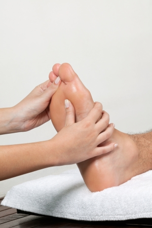 Foto de Close up of female masseuse massaging man s foot - Imagen libre de derechos