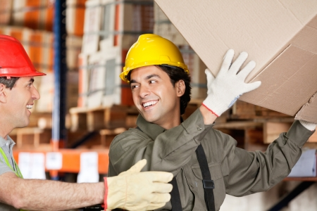 Happy foreman with coworker lifting cardboard box at warehouse