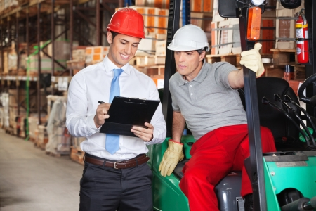 Photo pour Young supervisor showing clipboard to foreman at warehouse - image libre de droit