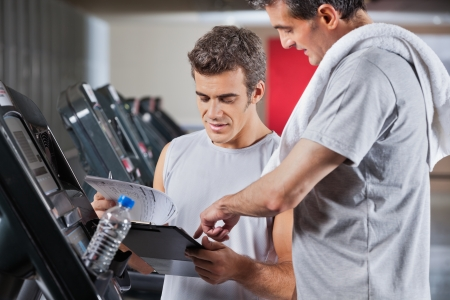 Instructor guiding man to fill the membership form of health club