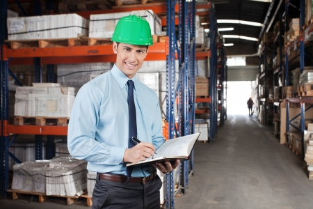 Portrait of confident young supervisor with book standing at warehouse