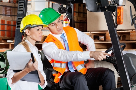 Male supervisor in forklift showing something to colleague with clipboard at warehouse