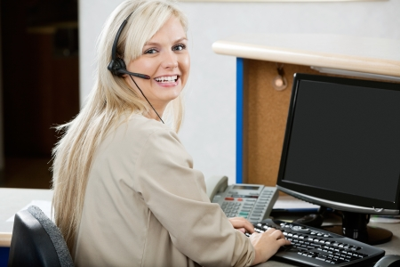 Cheerful Woman Using Computer At Reception Desk