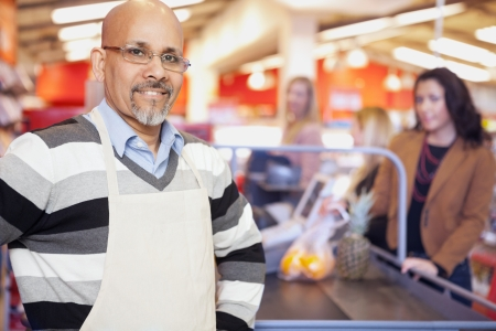 Grocery Store Cashier Standing At Checkout Counter