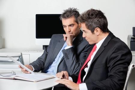 Photo pour Thoughtful Businessmen Using Digital Tablet At Desk - image libre de droit