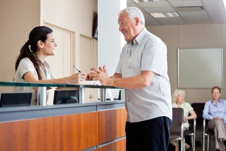 Photo pour Man Communicating With Female Receptionist - image libre de droit