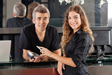 Hairdresser With Woman Paying Through Cellphone At Counter