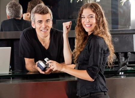 Happy Woman Paying Through Cellphone At Salon Counter