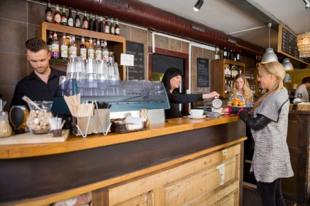 Female Bartender Serving Coffee To Customer At Counter