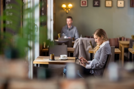 Side view of pregnant woman using digital tablet at cafe