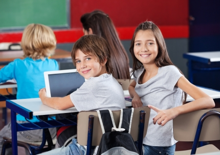 Photo for Schoolchildren With Digital Tablet Sitting In Classroom - Royalty Free Image