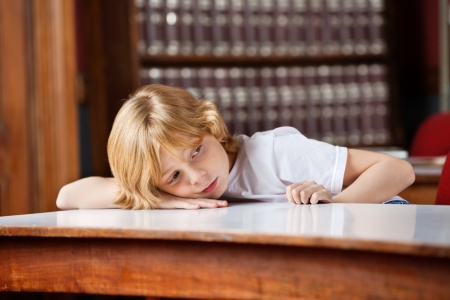 Thoughtful little schoolboy looking away while leaning on table in library