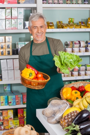 Portrait of senior salesman selling vegetables in supermarket