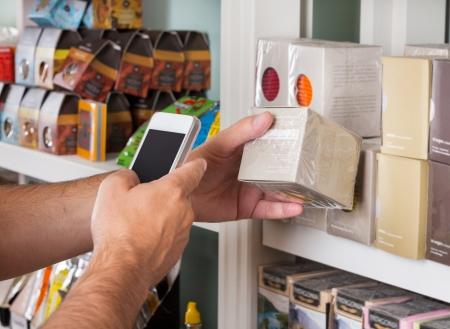 Photo pour Cropped image of man's hand scanning product through mobile phone - image libre de droit