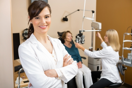 Portrait of young eye specialist with colleague examining patient in background
