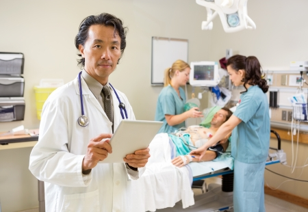 Portrait of mid adult doctor holding digital tablet while nurses treating male patient in hospital