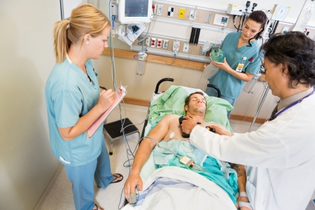 High angle view of doctor defibrillating critical patient while nurses standing by in hospital