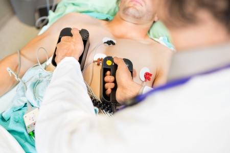 High angle view of doctor defibrillating male patient in hospital