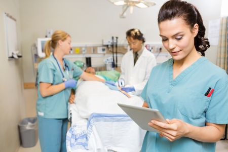 Beautiful nurse using digital tablet while doctor and colleague operating male patient in hospital