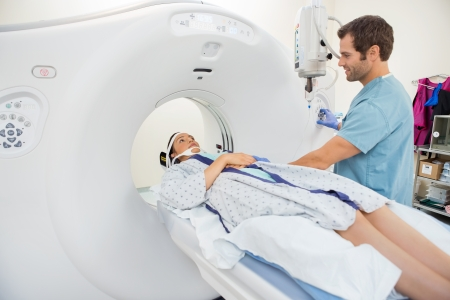 Male nurse preparing young patient for CT scan test in hospital room