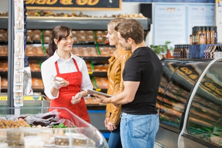 Photo pour Smiling saleswoman assisting couple in buying meat at butcher's shop - image libre de droit