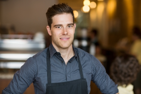Portrait of smiling young male owner standing in cafe