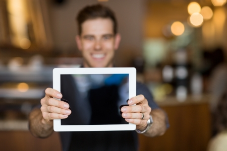 Photo for Male cafe owner showing digital tablet in cafeteria - Royalty Free Image