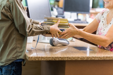 Midsection of young boy giving books to librarian at checkout counter in library