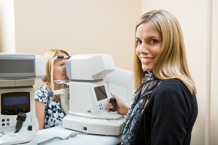 Young Optometrist measuring patients eye pressure with tonometer