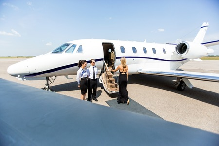 Elegant woman boarding private jet with airhostess and pilot at airport terminal