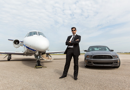 Photo pour Full length of confident businessman standing by car and private jet at airport terminal - image libre de droit