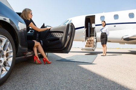 wealthy woman stepping out of car parked in front of private plane and airhostess
