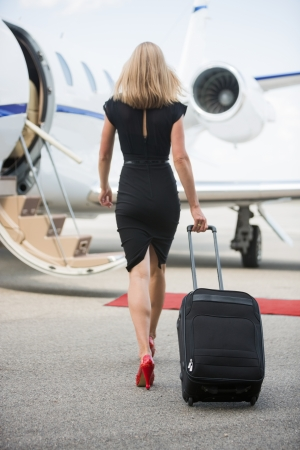 Full length rear view of wealthy woman with luggage walking towards private jet at airport terminal