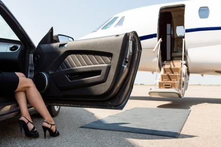 Low section of wealthy woman stepping out of car parked in front of private plane