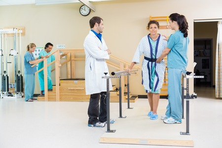 Physical therapists assisting female patient in walking with the support of handrails