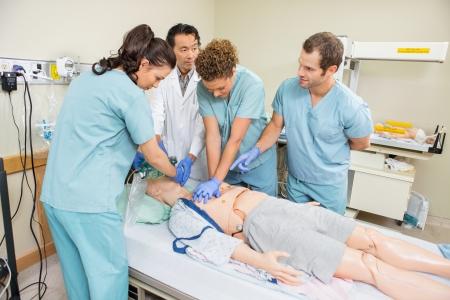 Photo pour Doctor and nurses performing CRP on dummy patient in hospital room - image libre de droit