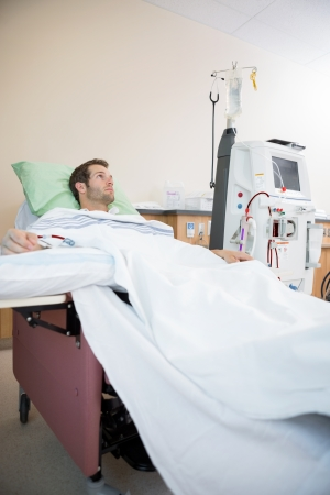 Young male patient looking away while receiving renal dialysis in hospital room