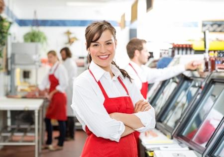 Photo pour Portrait of confident female butcher standing arms crossed with colleagues  - image libre de droit